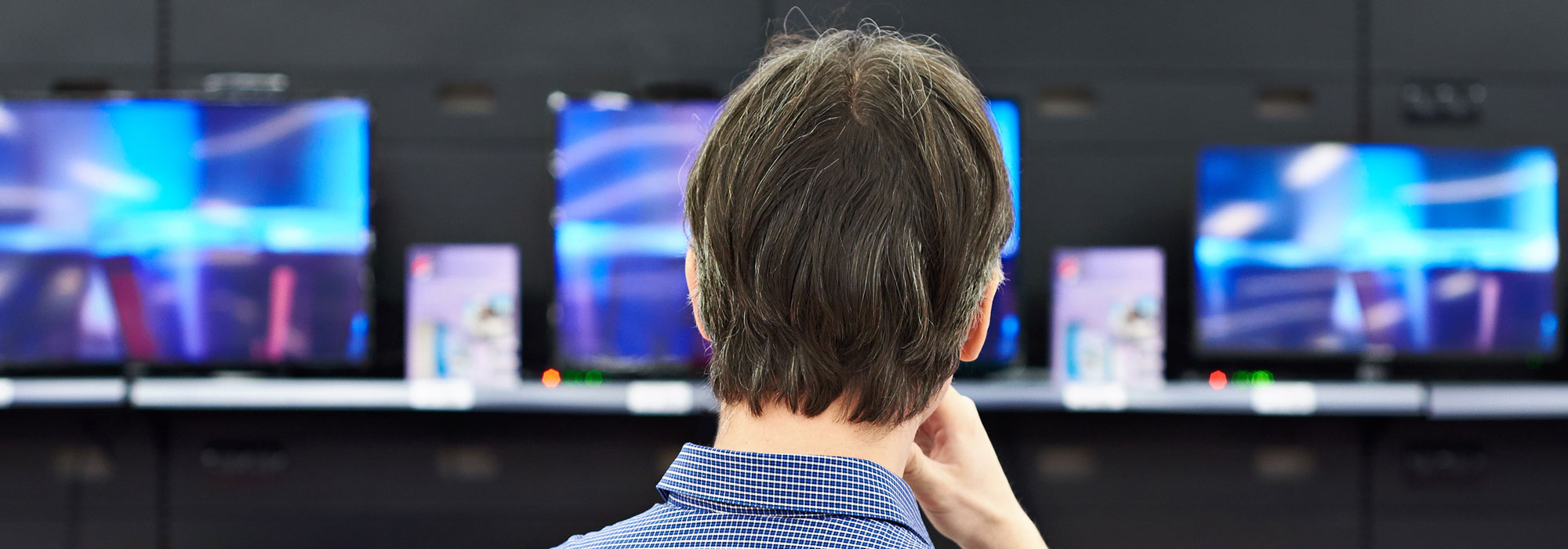man deciding on TVs