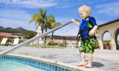 Little Boy Cautiously Stepping into Outdoor Pool in San Diego, C