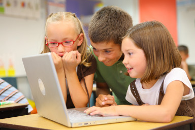 Elementary school students looking at computer 2