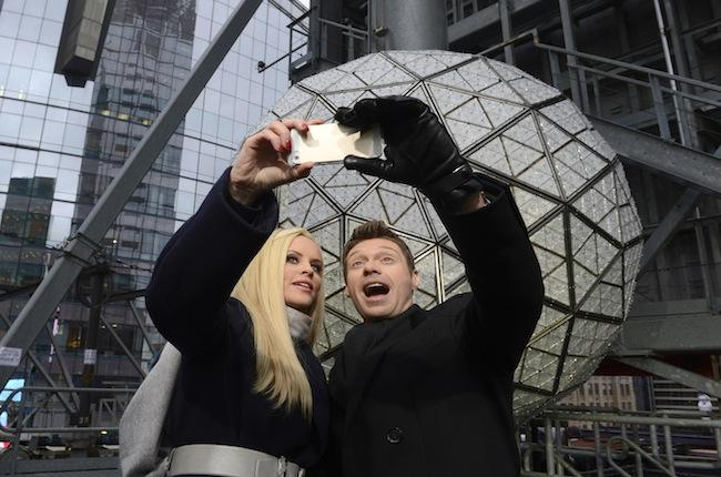 Ryan Seacrest and Jenny McCarthy pose for a selfie in front of the Waterford Crystal ball, atop One Times Square, that will ring in the New Year on Dick Clark's Rocking New Year's Eve. (ABC/Ida Mae Astute)