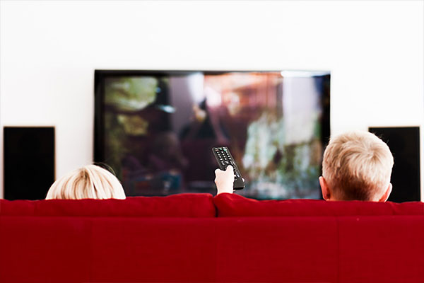 kids-looking-at-tv-red-couch