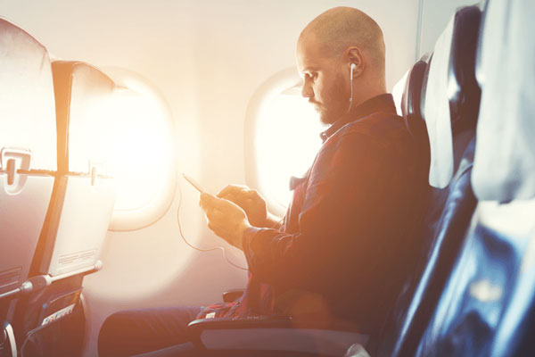 man searching for phone insurance on plane