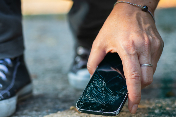 guy picking up cracked cellphone from ground