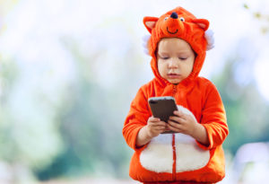 Child in Halloween costume holding a smartphone