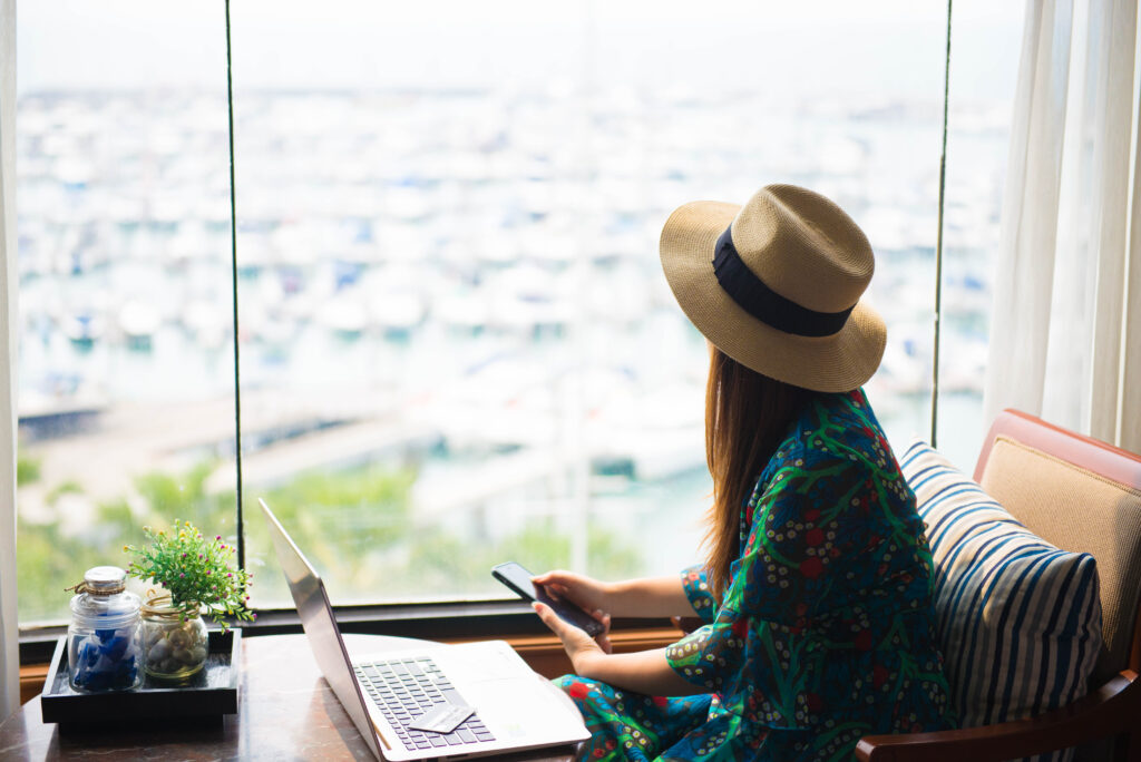 Woman on laptop in house on the beach